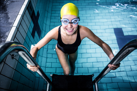 getting out: Smiling swimmer woman getting out of the swimming pool wearing swimming hat Stock Photo