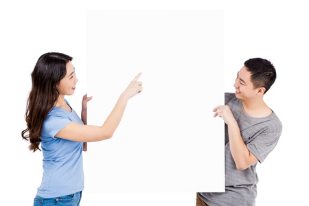 white poster: Happy young couple holding blank billboard against white background