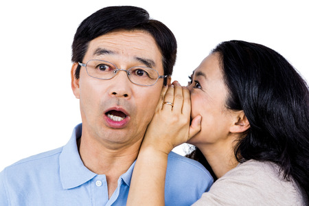 whispering: Woman whispering into shocked partners ear