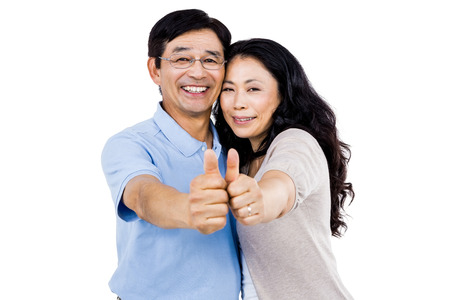 Smiling couple with thumbs up towards the camera