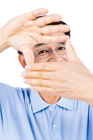 peep out: Portrait of man looking through hands against white background Stock Photo