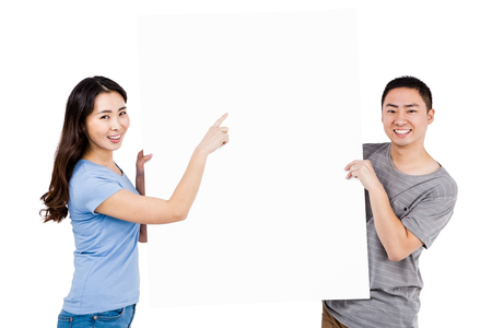 billboard background: Portrait of happy young couple holding blank billboard against white background