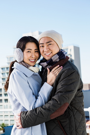 ear muff: Portrait of couple embracing against building Stock Photo