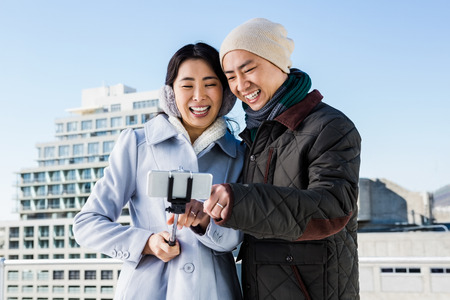 clicked: Couple laughing while viewing pictures clicked by them using smart phone