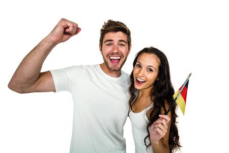 german flag: Portrait of smiling couple holding German flag on white screen
