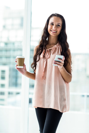 disposable cup: Smiling woman using smartphone holding disposable cup against window