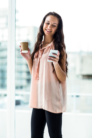 disposable cup: Smiling woman using smartphone holding disposable cup next to window Stock Photo