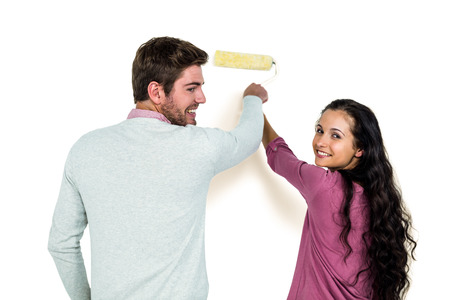 hair roller: Smiling couple holding paint roller against white background