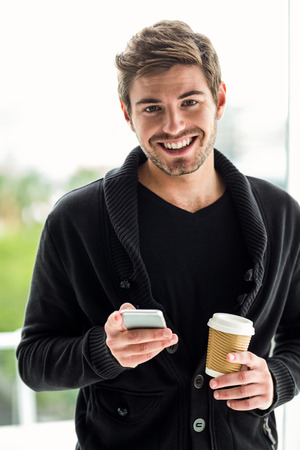 disposable cup: Handsome man using smartphone holding disposable cup looking at camera Stock Photo