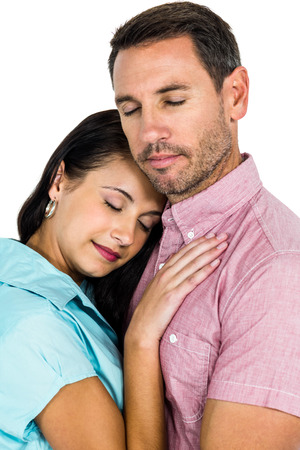 Peaceful couple hugging with eyes closed on white screen