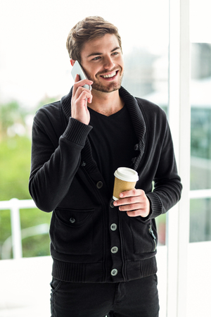disposable cup: Handsome man on phone call holding disposable cup in office Stock Photo