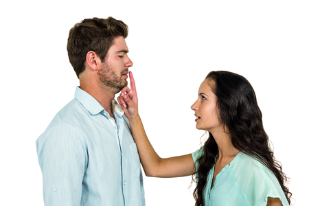 pareja discutiendo: Couple arguing while standing against white background