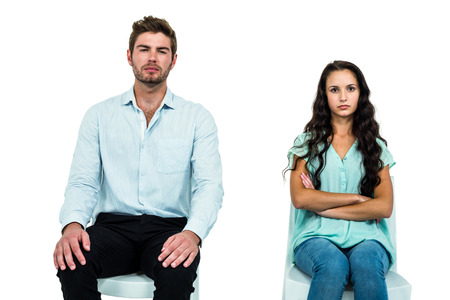 not talking: Couple sitting on chairs not talking after argument over white background