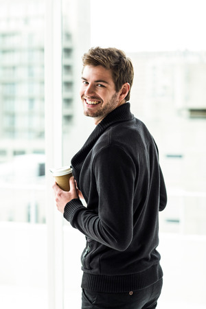 disposable cup: Handsome man holding disposable cup looking back to camera in office Stock Photo