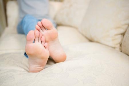 pies descalzos: Pies de la mujer en el sofá de casa