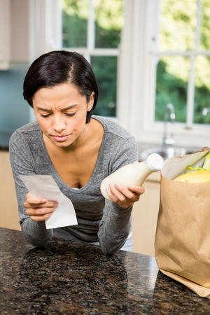 frowning: Frowning brunette holding receipt and milk in the kitchen