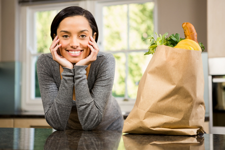 grocery bag: Smiling brunette with  grocery bag on counter in kitchen