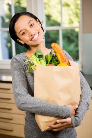 grocery bag: Smiling brunette holding grocery bag in kitchen