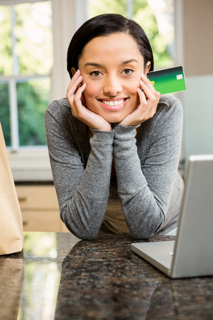 household money: Smiling brunette in kitchen holding credit card with grocery bag and laptop on counter