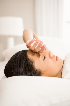 Frowning brunette in bed with hand on face Stock Photo