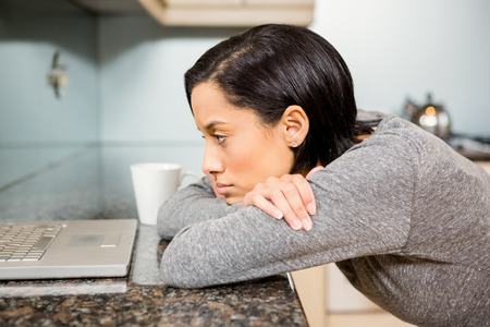 domicile: Upset brunette looking at laptop in the kitchen