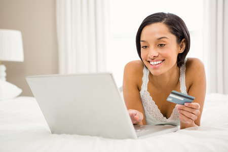 household money: Smiling brunette using laptop and holding credit card on the bed