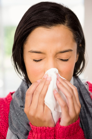 sneezing: Attractive brunette sneezing at home Stock Photo