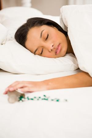 knocked over: Brunette sleeping in bed by spilt bottle of pills at home Stock Photo