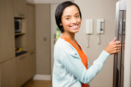 refrigerator kitchen: Smiling brunette with hand on refrigerator in the kitchen
