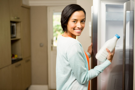 refrigerator kitchen: Smiling brunette holding milk bottle with open refrigerator in the kitchen Stock Photo