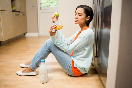 unsettled: Unsettled brunette holding apple and dessert sitting on the floor in the kitchen