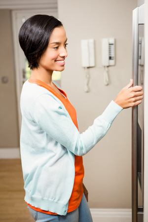 refrigerator: Smiling brunette with hand on refrigerator in the kitchen