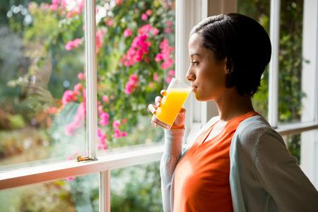 orange juice glass: Thoughtful brunette drinking orange juice near the window