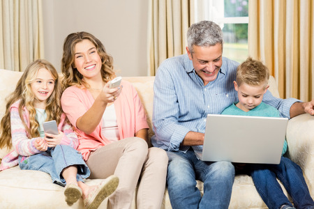 female child: Happy family enjoying a movie together at home