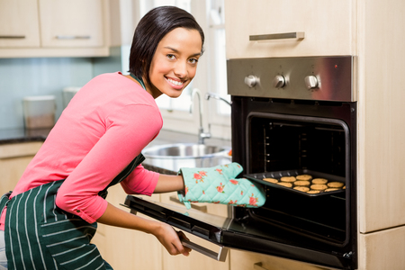 woman baking: Smiling woman baking biscuits at home