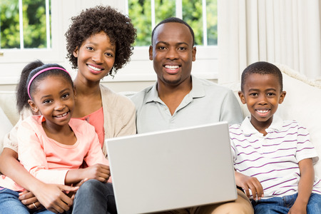 family sofa: Happy family using laptop on the sofa in living room