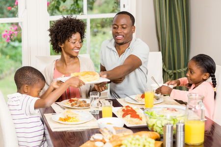 Happy family eating together at home Stock Photo