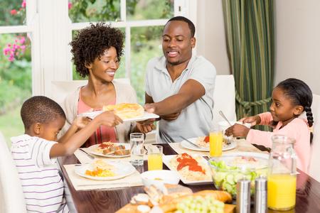 comiendo: La familia feliz comiendo juntos en casa Foto de archivo
