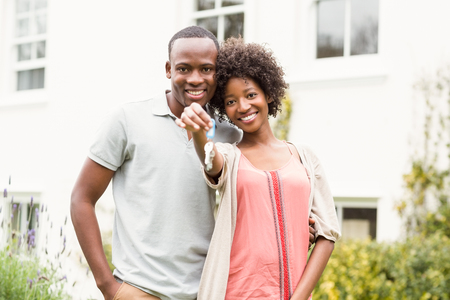 home keys: Smiling couple holding keys to their house