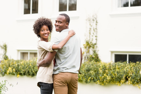 black couple: Smiling couple looking back at the camera in front of their home