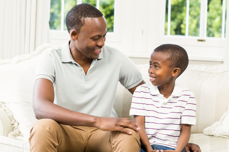 one parent: Father and son sitting on the couch in the living room Stock Photo