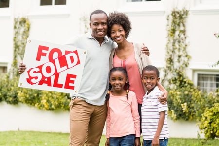 sold sign: Happy family standing together while holding a sold sign Stock Photo