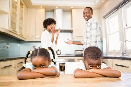 dreariness: Sad siblings against parents arguing in kitchen