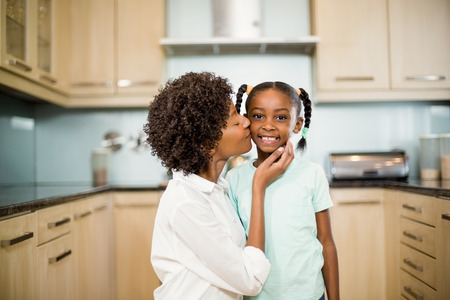 mother kissing daughter: Mother kissing daughter in the kitchen Stock Photo
