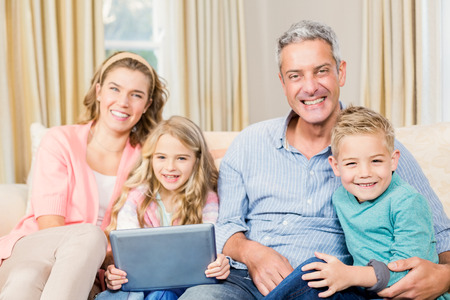 family sofa: Happy family using tablet on the sofa in the living room Stock Photo