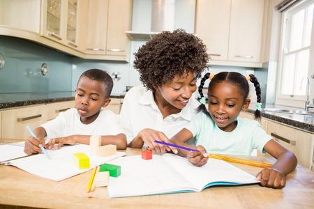 black hair woman: Mother checking children homework in the kitchen Stock Photo