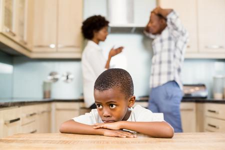 problemas familiares: El muchacho triste contra padres discutiendo en la cocina