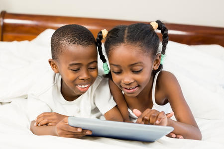 girl with black hair: Brother and sister lying in the bed using tablet