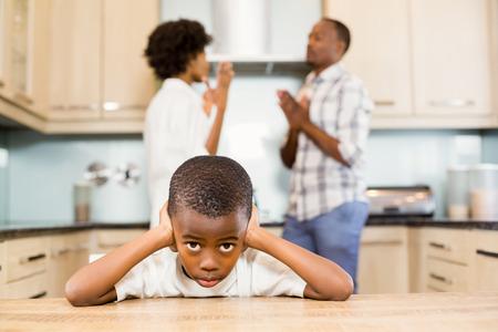 desolaci�n: El muchacho triste contra padres discutiendo en la cocina