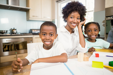 ni�os ayudando: Mother helping children do their homework in the kitchen